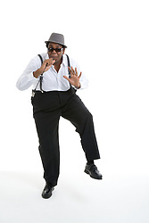 Man dressed in Blues Brothers fancy dress costume singing into a microphone,