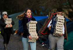© Licensed to London News Pictures. 23/01/2016. Dunkirk, France. Aid workers carrying eggs walk through the migrant camp in Dunkirk, northern France where Leader of the Labour Party JEREMY CORBYN is due to visits today (Sat). Thousands of migrants and refugees at living in temporary accommodation as they attempt to reach the UK. Photo credit: Ben Cawthra/LNP