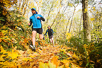 Two men trail running through a forest in the Fall colors. St Edwards State Park, in Kenmore, Washington.