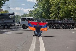 A local teen sits in front of the Baghramyan Street blockade with his Armenian flag on the day of Serzh Sargsyan's resignation