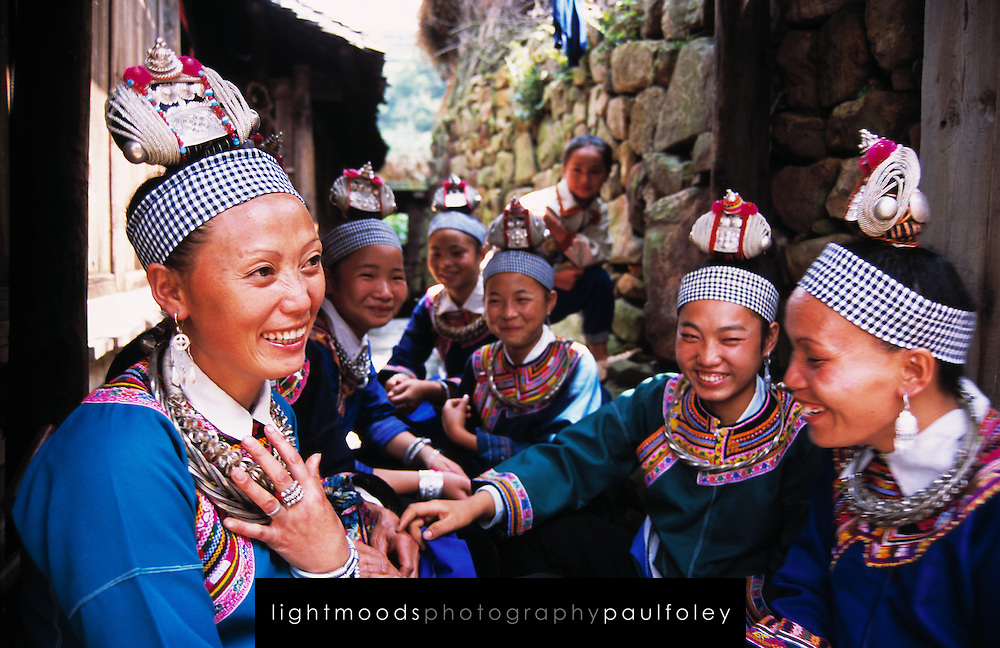Smiling Miao woman and young girls in traditional costume, Duyun, Guizhou Province, China