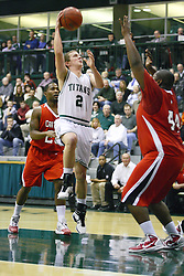 29 January 2011: Sean Johnson uses the hook to get a shot past Raul Guzman during an NCAA basketball game between the Carthage Reds and the Illinois Wesleyan Titans at Shirk Center in Bloomington Illinois.