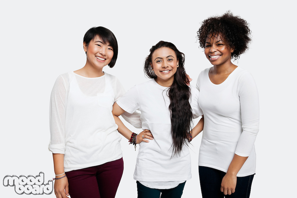 Portrait of young multi-ethnic female friends in casuals smiling over white background