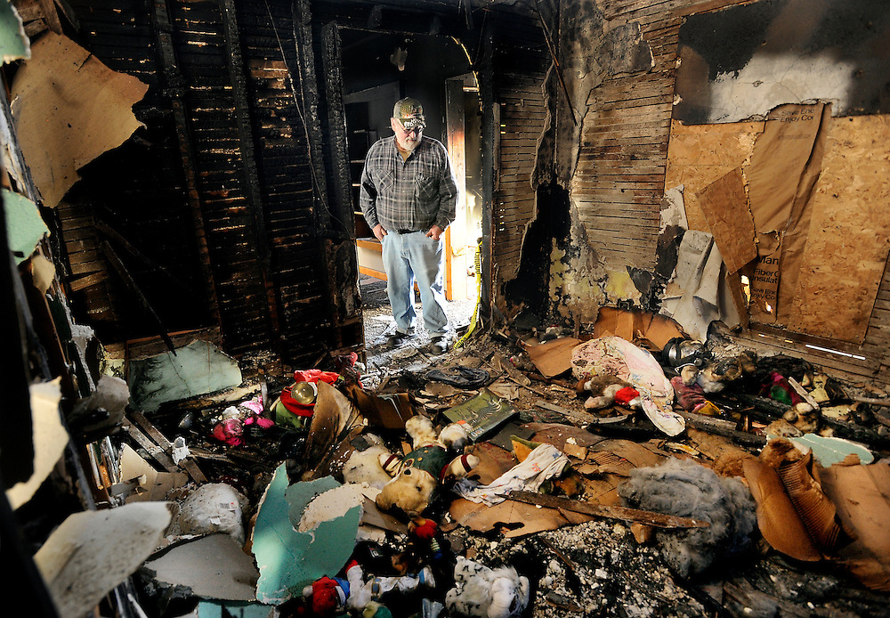 Gary Nipp looks down at the debris in a room where a fire started and totaled his home. After being two days late on his home insurance, he received no coverage for the home where he and his family lived.