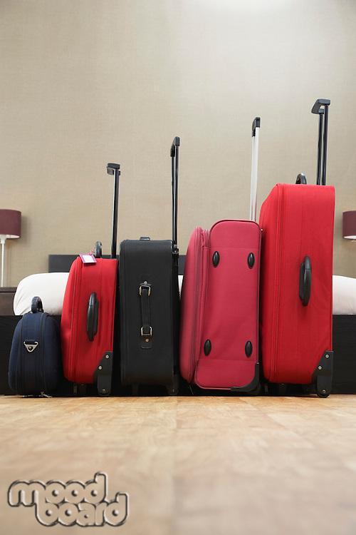 Suitcases standing in row in bedroom