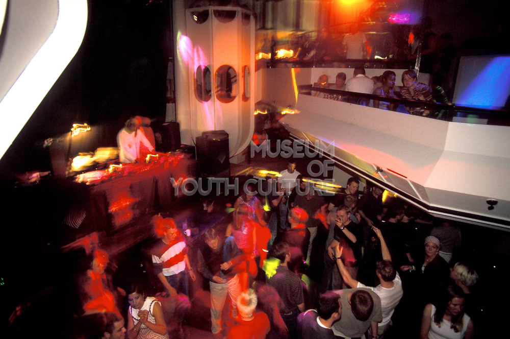 DJ and crowd dancing in a club.