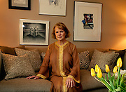 Red haired adult woman wearing a caftan seated on her sofa.  yellow tulips in the foreground. Slight smile, sideways glance.