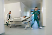Medical Workers Moving Patient on gurney through hospital corridor motion blur