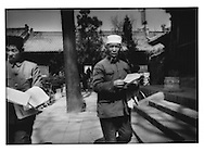 Hui Muslim man accepts a leaflet in the garden of the Great Mosque (Daqingzhen Si) of Xian built in Chinese temple style in the 18th century, Xian, China.   Xian was both China's ancient capital and the terminus of the Silk Road.