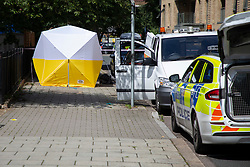 © Licensed to London News Pictures. 12/07/2020. London, UK. A forensics tent at a crime scene on the Black Prince Estate in Kennington. Police were called shortly after 2200hrs on Saturday, 11 July, to a man stabbed on the Black Prince Estate in Kennington. Officers attended along with London Ambulance Service and found a 30-year-old man suffering stab injuries. Despite the efforts of officers and paramedics, the man was pronounced dead at the scene. Photo credit: George Cracknell Wright/LNP