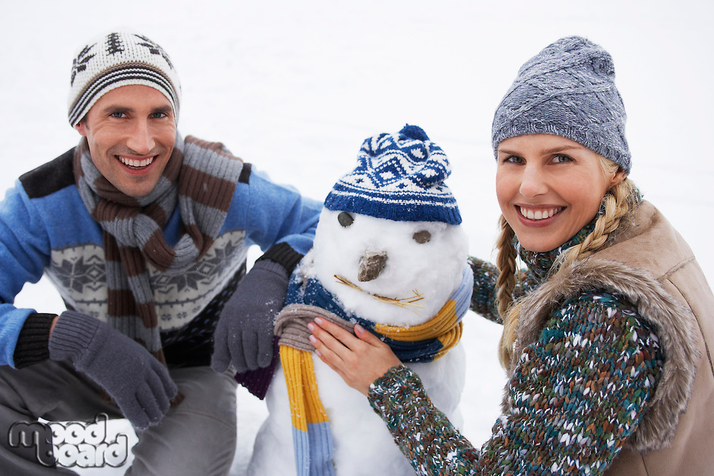 Couple dressing snowman crouching in snow portrait