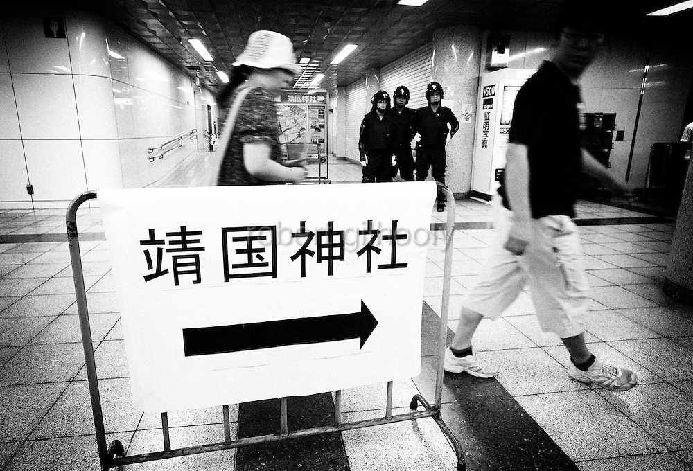 A sign points pilgrims to Yasukuni Shrine as riot police look on at an underground station near the shrine in Tokyo, Japan on 15 Aug. 2008. Wartime prime minister Hideki Tojo - who ordered the attack on Peal Harbor and was charged and hanged as a war criminal after World War II, is enshrined inside the controversial Yasukuni Shrine together with 13 other convicted war criminals, a fact that still angers citizens in China and South Korea, both of which fell vicim to Japan's wartime activities. Aug 15. is the anniversary of Japan's surrender in World War II and 100s of thousands of pilgrims from around the country visit the shrine. ..Photographer: Robert Gilhooly