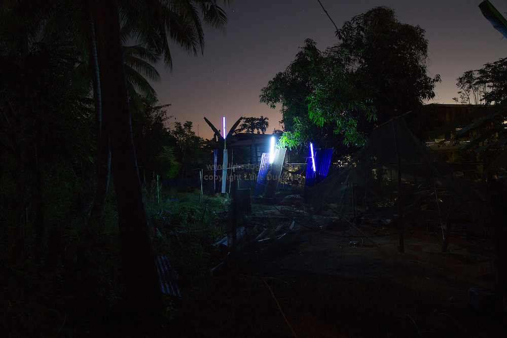 Insect traps set-up on a villagers garden in a remote village. With lights left on all night the villagers will collect what has fallen into a bucket before dawn.<br /> <br /> Due to an increase in the use of insecticide in Thailand many villages have abandoned trying to catch insects naturally. Nong Plaa Dak Yai in Buriram Province is one of the exceptions with locals catching hundreds of kilo's per year simply by switching a neon light on overnight.<br /> <br /> The western world cringes at the thought of eating insects. But in other parts of the world it is a common and popular addition to peoples daily intake. Granted most of this exists on a small-scale, with local villagers catching for their own consumption, still worldwide 1500 species of insects are eaten.<br /> <br /> But no-where else like Thailand has it become a multi-million dollar industry. Thailand leads the way in the world for large scale industrial breeding farms of certain types of insects specifally for the consumer market. Crickets alone are now bred by over 20,000 farmers in the Northeast of the country and Makro supermarket chain sells frozen bags of insects from crickets to grubs. Even a University in a Provincial town has a faculty that studies the rearing of different insects for industrialised production.<br /> <br /> Entomophagy, the eating of insects, has in the last few years become a popular topic because it is seriously being seen as a means of helping in the worlds food shortages at a time when the weather is becoming ever more erratic. <br /> <br /> In 2013 the FAO released a large report on entomology and how Thailand&rsquo;s model could be replicated in other countries. But first the perception of eating insects in developed nations needs to change.