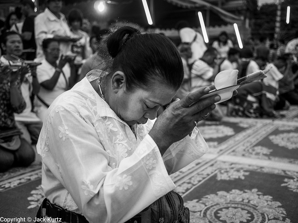 "15 MARCH 2014 - NAKHON CHAI SI, NAKHON PATHOM, THAILAND: A woman prays at the beginning of the Wat Bang Phra tattoo festival. Wat Bang Phra is the best known ""Sak Yant"" tattoo temple in Thailand. It's located in Nakhon Pathom province, about 40 miles from Bangkok. The tattoos are given with hollow stainless steel needles and are thought to possess magical powers of protection. The tattoos, which are given by Buddhist monks, are popular with soldiers, policeman and gangsters, people who generally live in harm's way. The tattoo must be activated to remain powerful and the annual Wai Khru Ceremony (tattoo festival) at the temple draws thousands of devotees who come to the temple to activate or renew the tattoos. People go into trance like states and then assume the personality of their tattoo, so people with tiger tattoos assume the personality of a tiger, people with monkey tattoos take on the personality of a monkey and so on. In recent years the tattoo festival has become popular with tourists who make the trip to Nakorn Pathom province to see a side of ""exotic"" Thailand.   PHOTO BY JACK KURTZ"