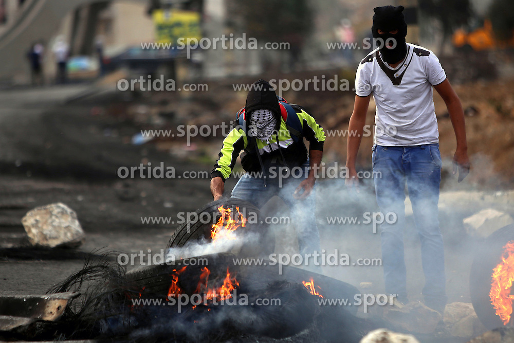 19.10.2015, Ramallah, PSE, Nahostkonflikt zwischen Israel und Pal&auml;stina, im Bild Zusammenst&ouml;sse zwischen Pal&auml;stinensischen Demonstranten und Israelischen Sicherheitskr&auml;fte // A masked Palestinian protester burns tires during clashes with Israeli borderguards next to the Jewish settlement of Beit El. More than two weeks of unrest have raised warnings of the risk of a full-scale Palestinian uprising, while some Israeli politicians have urged residents to arm themselves to fend off the threat of stabbings and gun assaults, Palestine on 2015/10/19. EXPA Pictures &copy; 2015, PhotoCredit: EXPA/ APAimages/ Shadi Hatem<br /> <br /> *****ATTENTION - for AUT, GER, SUI, ITA, POL, CRO, SRB only*****