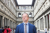 FLORENCE, ITALY - 29 JUNE 2016: The new director of the Uffizi Gallery Eike Schmidt poses for a portait in the courtyard of the Uffizi Gallery in Florence, Italy, on June 29th 2016.<br /> <br /> Art historian Eike Schmidt, former curator and head of the Department of Sculpture, Applied Art and Textiles at the Minneapolis Institute of Arts, became the first non-Italian director of the Uffizi in August 2015, replacing Antonio Natali who directed the gallery for 9 years. One of the main goals of the new director is to open the Vasari Corridor to the general public. Currently the corridor can only be visited with group reservations made by external tour and travel agencies throughout the year.<br /> <br /> The Vasari Corridor is is a 1-kilometer-long (more than half mile) elevated enclosed passageway which connects the Palazzo Vecchio with the Palazzo Pitti, passing through the Uffizi Gallery and crossing the Ponte Vecchio above the Arno River, in Florence. The passageway was designed and built in 1564 by Giorgio Vasari in only 6 months to allow Cosimo de' Medici and other Florentine elite to walk safely through the city, from the seat of power in Palazzo Vecchio to their private residence, Palazzo Pitti. The passageway contains over 1000 paintings, dating from the 17th and 18th centuries, including the largest and very important collection of self-portraits by some of the most famous masters of painting from the 16th to the 20th century, including Filippo Lippi, Rembrandt, Velazquez, Delacroix and Ensor.