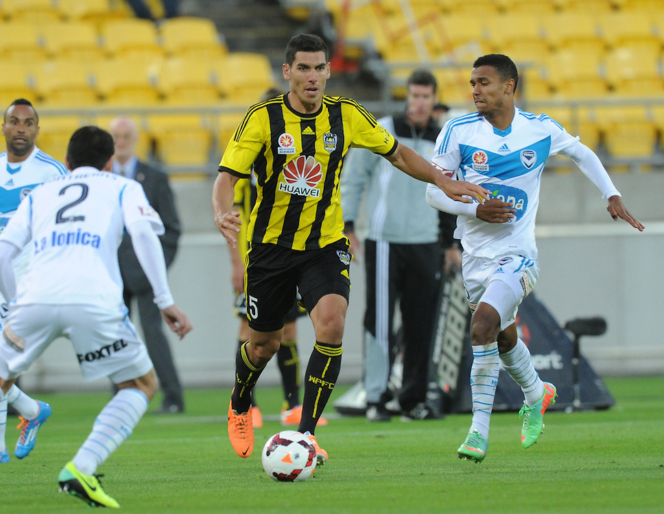 Phoenix's Michael Boxall, centre, attempts to splt the Melbourne Victory FC defence in the A-League football match at Westpac Stadium, Wellington, New Zealand, Saturday, Januray 18, 2014. Credit:SNPA / Ross Setford