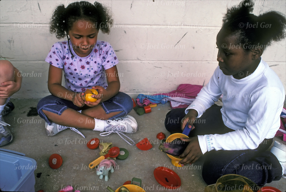 Young preschool children playing with plastic toy animals