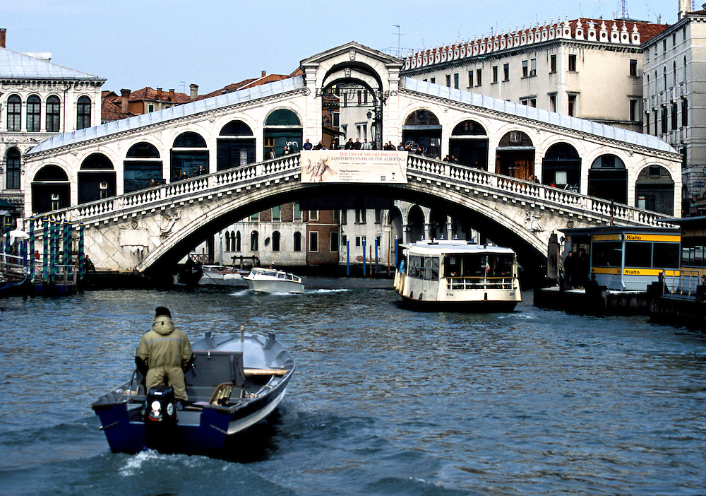 Working motor boat, with a standing man at the tiller, chugs toward the Rialto Bridge and the Rialto vaporetto stop, from which one ACTV vaporetto is leaving to go under the bridge and a speedboat churns toward us, lifting a considerable wake.