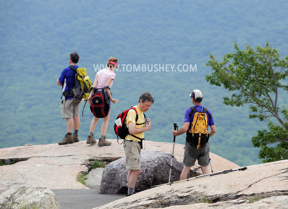 Bear Mountain, New York - A man, at left, enjoys the view while his companion takes off her backpack after hiking up the Appalachian Trail at Bear Mountain on June 5, 2010. The two men at right are preparing to hike back down the mountain.