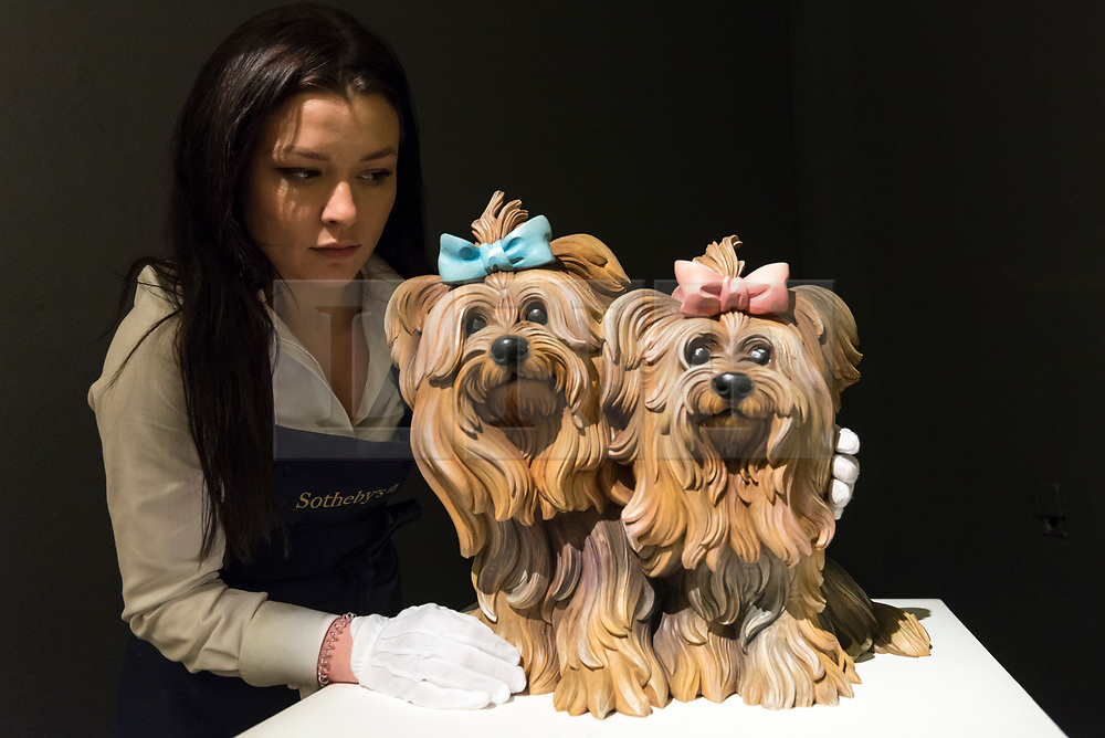© Licensed to London News Pictures. 01/03/2019. LONDON, UK. A technician examines ''Yorkshire Terriers'', 1991, by Jeff Koons, (Est. £600,000 - 800,000).  Preview of Sotheby's Contemporary Art Sale in their New Bond Street galleries.  Works by artists including Tracey Emin, Jenny Saville, Jean-Michel Basquiat and Andy Warhol will be offered for auction on 5 March 2019.  Photo credit: Stephen Chung/LNP
