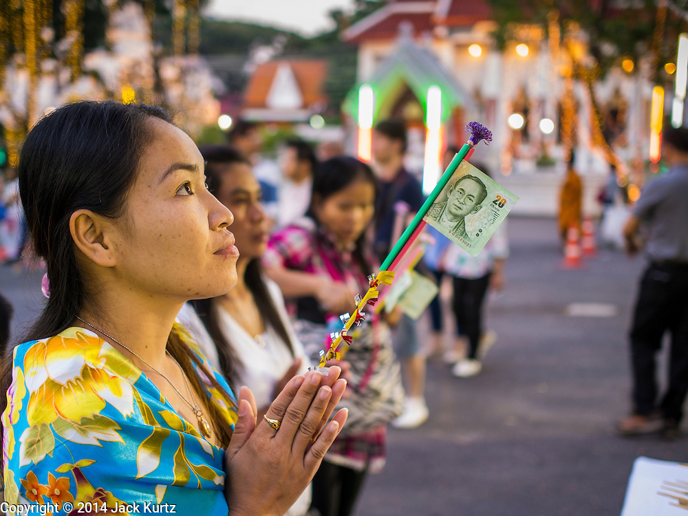 31 DECEMBER 2014 - BANGKOK, THAILAND: People pray on New Year's Eve at Wat Pathum Wanaram in Bangkok. Hundreds of thousands of people pack into the Ratchaprasong Intersection in Bangkok for the city's annual New Year's Eve countdown. Many Thais go the Erawan Shrine and Wat Pathum Wanaram near the intersection to pray and make merit before going to their New Year's parties.    PHOTO BY JACK KURTZ