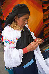 South America, Ecuador, Otavalo,  Plaza de Ponchos, female vendor crocheting at the Saturday textile and crafts market, one of the largest in the world.