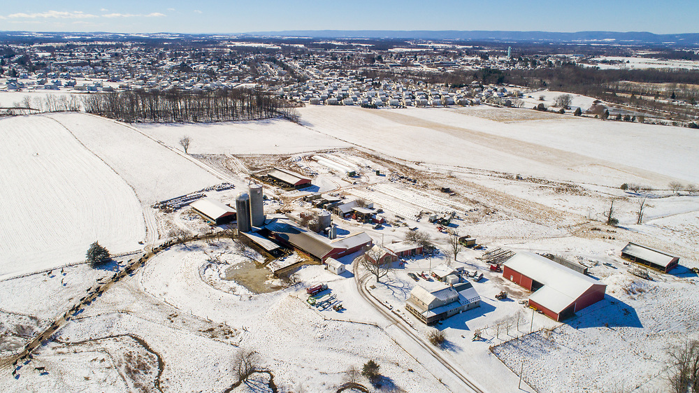Aerial view of working dairy farm on a snowy day with suburban sprawl touching at the edges of the property, Taneytown, Maryland