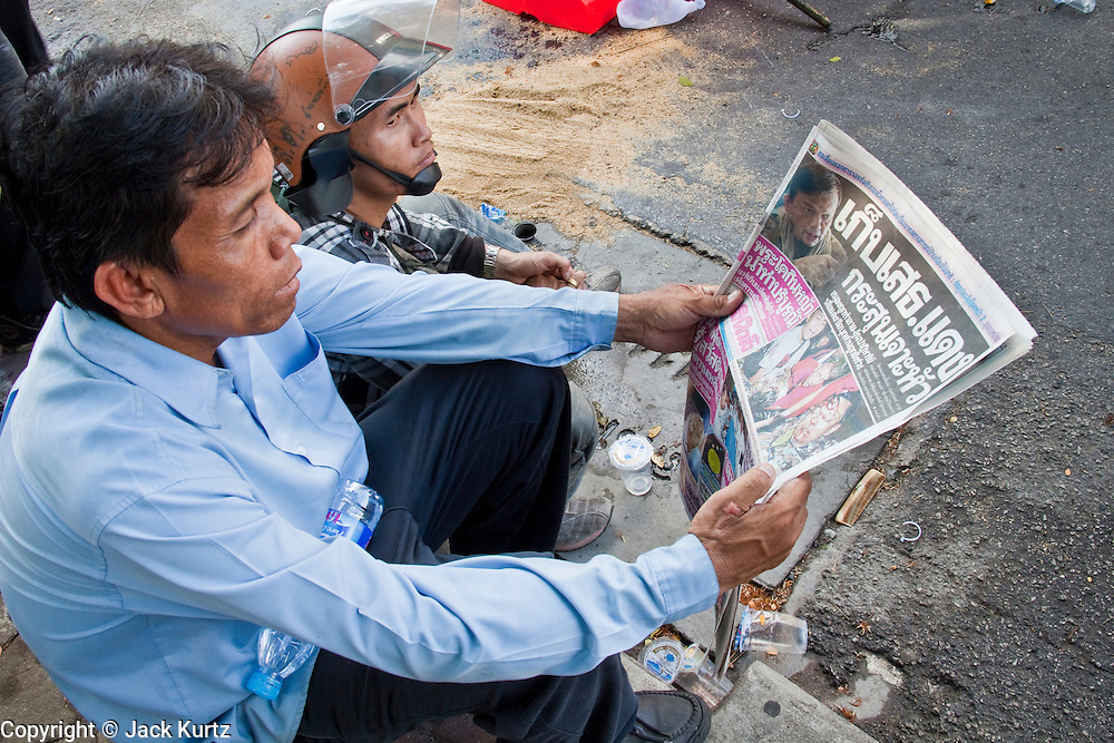 14 MAY 2010 - BANGKOK, THAILAND: Anti government protesters read about the shooting of Red Shirt hero and unofficial military leader Seh Daeng in a Thai newspaper at Red Shirt roadblock at the intersection of Rama IV and Witthayu Roads in Bangkok Friday morning. Tensions among Red Shirt protesters demanding the dissolution of the current Thai government rose overnight after Seh Daeng, the Red Shirt's unofficial military leader was shot in the head by a sniper. Gangs of Red Shirts have taken over military checkpoints on Rama IV and are firing small rockets at military helicopters and army patrols in the area. Troops have responded by firing towards posters.  PHOTO BY JACK KURTZ