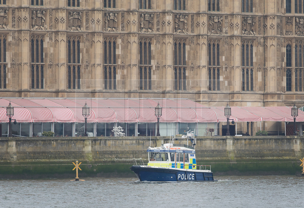 © Licensed to London News Pictures.23/03/2017.London, UK. A police launch boat passes Parliament on the River Thames as Prime Minister Theresa May speaks to Parliament, the day after a lone terrorist killed 4 people and injured several more, in an attack using a car and a knife. The attacker managed to gain entry to the grounds of the Houses of Parliament, killing one police officer.Photo credit: Peter Macdiarmid/LNP