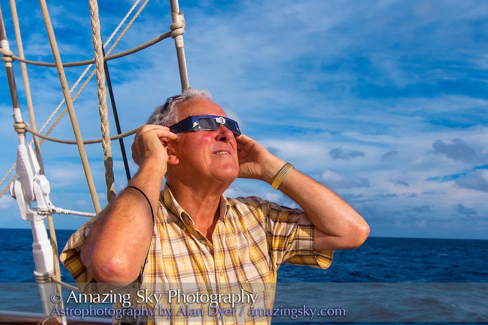 Eclipse chaser watching the partial phases of the total eclipse of the Sun, November 3, 2013, from the deck of the Star Flyer sailing ship.