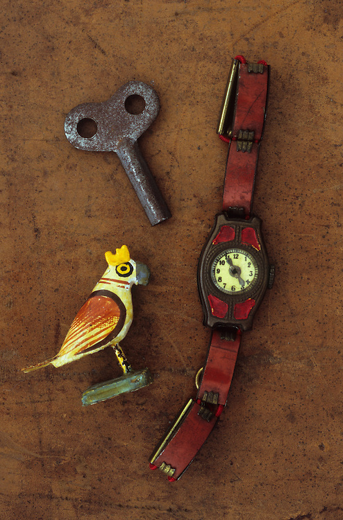 Childs vintage tin watch lying on scuffed leather next to rusty key from clockwork toy and model of bird