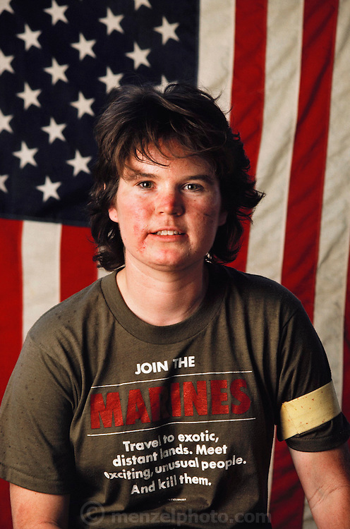 "A young woman war games paintball combatant at Sad Sack's Paintball Park, near Los Angeles, California, USA. Her T-shirt reads: ""Join the Marines. Travel to exotic distant lands. Meet exciting, unusual people. And kill them."" MODEL RELEASED."