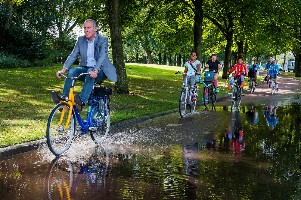 Nederland, Rotterdam, 20170831<br /> Na een flinke stortbui zorgt een grote plas op het fietspad  voor vrolijke beelden als de fietsers gedwongen worden hun voeten omhoog te houden als ze niet nat willen worden. <br /> <br /> Foto: (c) Michiel Wijnbergh