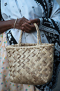 Woman holding hand made palm leaf basket. Clemencia.