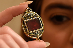 """© Licensed to London News Pictures. 23/03/2017. London, UK.   A staff member shows """"The Fettercairn Jewel"""", enamelled gold, set with an almandine garnet (est. GBP 30-50k).  Preview at Sotheby's New Bond Street of property from two great Scottish families, the Forbeses of Pitsligo and the Marquesses of Lothian, which will be auctioned in London on 28 March.   Photo credit : Stephen Chung/LNP"""