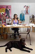 """Elizabeth Hurley with her swimwear designs in her studio in South Kensington, London, UK. Sold exclusively in Harrods and Saks in New York. Also featured in the shot is Liz's dog """"Lucy""""."""