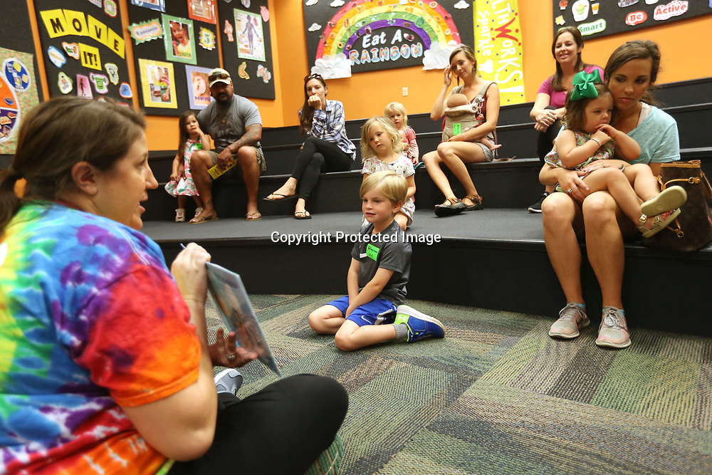 "Jessie Leddy, Captain of the Universe at Healthworks!, reads to kids and their parents Monday morning during the ""We Love Our Moms!"" Hip Hoppers session at Healthworks!. Hip Hoppers are preschool age kids that meet twice a month year round."