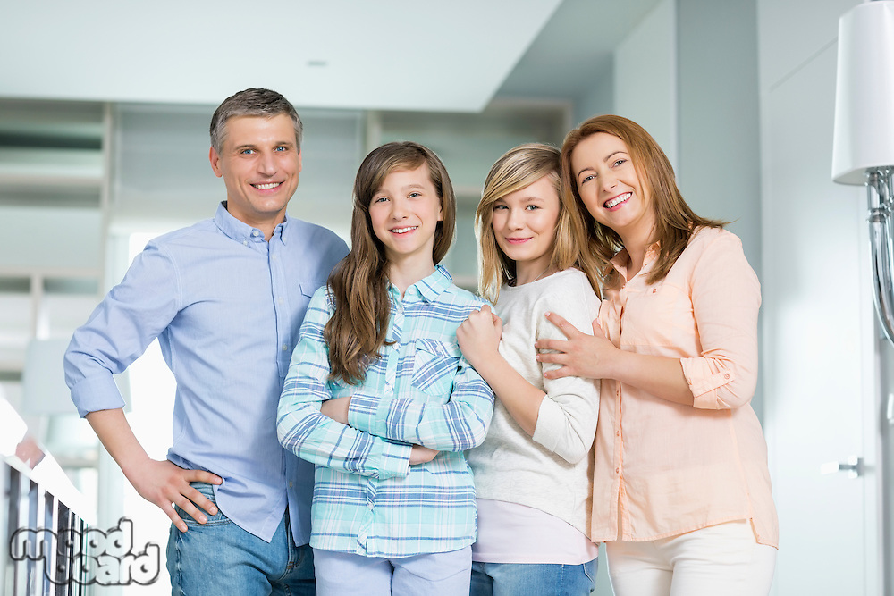 Portrait of happy family with children standing together at home