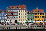 Tourists relaxing and enjoying the blue skies of summer in the Nyhavn area of Copenhagen, Denmark.
