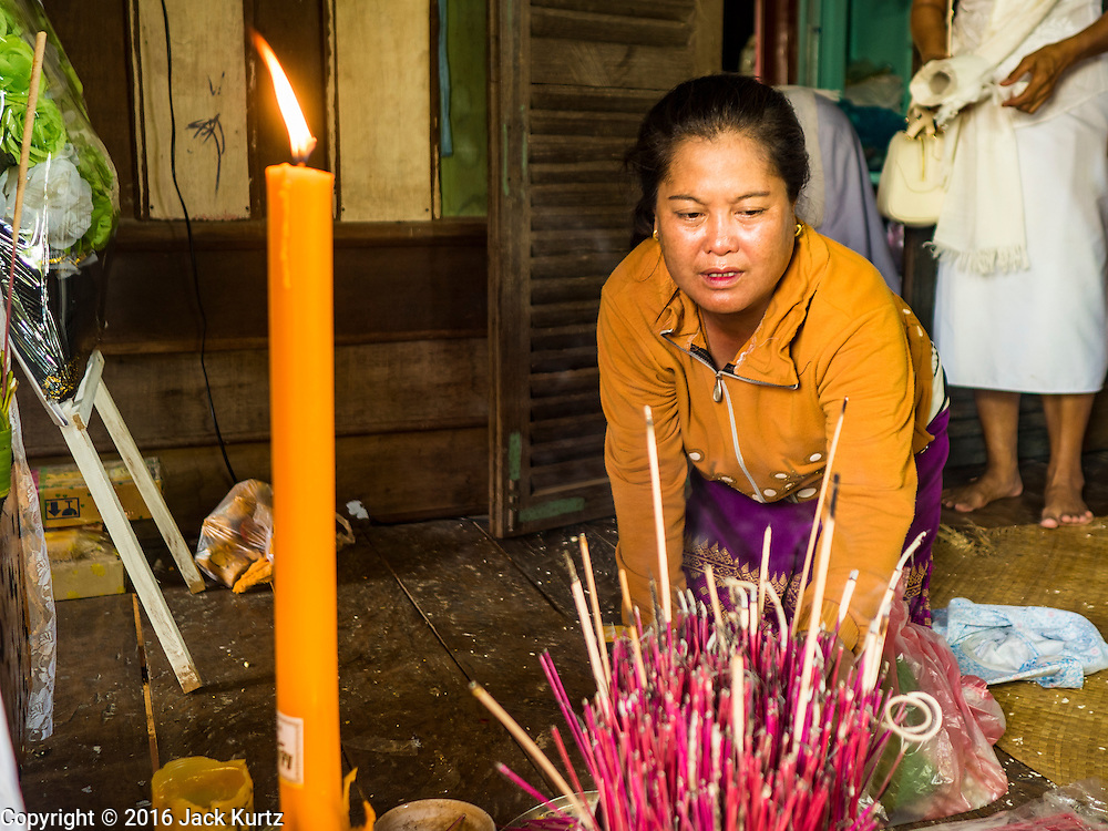 20 JUNE 2016 - DON KHONE, CHAMPASAK, LAOS: A mourner lights incense at a funeral at a private home in Don Khone village on Don Khone Island. Don Khone Island, one of the larger islands in the 4,000 Islands chain on the Mekong River in southern Laos. The island has become a backpacker hot spot, there are lots of guest houses and small restaurants on the north end of the island.     PHOTO BY JACK KURTZ