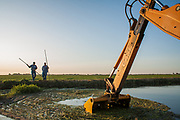 Jose Torres (R) and Felipe Munoz of the Columbia Canal Company work to clear irrigation ditches near Mendota so that water can flow to farmers fields. August 7, 2009.