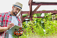 Portrait of mature man examining plants growing in garden while writing report on clipboard