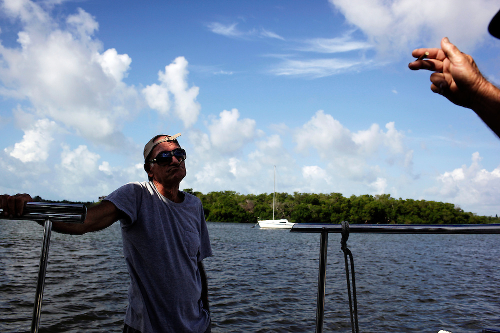 A man by the nickname of Hillbilly Jim, left, who lives on a boat anchored in Estero Bay, Fla. talks with Randy Eibler, who has lived on a boat for 34 years. Eibler said for the most part, people who live on their boats tend to anchor near each other to form a community and watch out for one another.