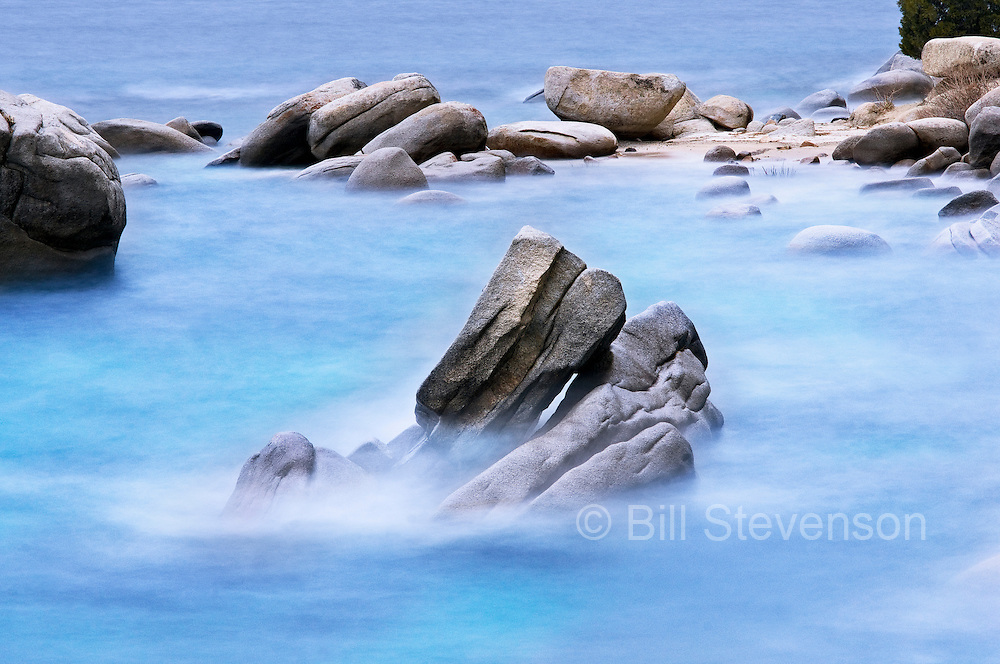 This landscape image was created on a cloudy, windy day. The misty look is the result of leaving the shutter open for about 30 seconds as the waves rolled through the frame. All that's left of the waves is the ghost image as they pass in front of the rock.
