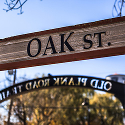 Photo of Oak Street sign in Frankfort Illinois with the Old Plank Road Trail sign in the background. Frankfort is a Southwest Chicago suburb. The Old Plank Road Trail is a 22 mile long public path and former railroad track train route that runs through Frankfort.