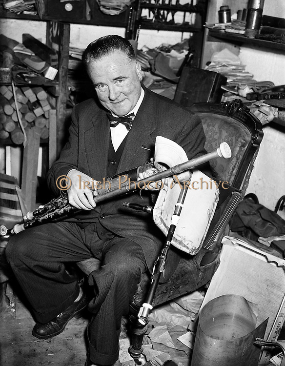 "Leo Rowsome making pipes at 9 Belton Park Road.16/06/56..Leo Rowsome (05/04/1903 - 20/09/1970) was the third generation of an unbroken line of uilleann pipers. He was performer, manufacturer and teacher of the uilleann pipes - the complete master of his instrument. He devoted his entire life to the uilleann pipes..Samuel Rowsome, Leo's grandfather sent his sons, John, Thomas and William to a German teacher of music who resided in Ferns, near their home in Co. Wexford to learn the theory of music and how to play various instruments. This knowledge was passed on through William to his son, Leo who made good use of it in his teaching, writing music for his many pupils..Leo was born in Harold's Cross, Dublin in 1903. His father, William realised that his son had the ability to become a talented musician and craftsman. Constantly watching his father making and repairing instruments, Leo learned the art of pipe making and instrument repair. So rapid was his progress at piping that in 1919 at the age of sixteen he was appointed teacher of the uilleann pipes at Dublin's Municipal School of Music (now D.I.T. Conservatory of Music & Drama) for 50 years. He also taught at Dublin's Pipers Club of which he was President..In 1925, Leo's father died at the age of fifty-five. Leo successfully carried on the family business, after completing his own set of pipes in 1926. The instrument remained an object of fascination and veneration for countless audiences at home and abroad..Leo was the first uilleann piper to perform on Irish National Radio in the early 1920s when he played solo and later in duets with Frank O'Higgins (fiddle), Micheal O Duinn (fiddle) and Leo's brother John (fiddle). Leo's ""All Ireland Trio"" comprised Neilus Cronin, flute, Seamus O'Mahony, fiddle and Leo pipes. He formed his Pipes Quartet in the mid 1930s and broadcast regularly throughout the 1940s/50s. Leo was the first Irish artist to perform on BBC T.V. (1933). He made many recordings for Dec"