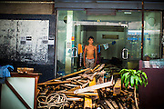 "12 DECEMBER 2012 - BANGKOK, THAILAND: A worker stands in the doorway of the former brothel he lives in at ""Washington Square"" a notorious entertainment district off Sukhumvit Soi 22 in Bangkok. Demolition workers on many projects in Thailand live on their job site tearing down the building and recycling what can recycled as they do so until the site is no longer inhabitable. They sleep on the floors in the buildings or sometimes in tents, cooking on gas or charcoal stoves working from morning till dark. Sometimes families live and work together, other times just men. Washington Square was one of Bangkok's oldest red light districts. It was closed early 2012 and is being torn down to make way for redevelopment.    PHOTO BY JACK KURTZ"