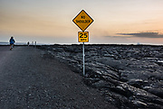"Bicyclists pedal through a barren black landscape on emergency road/Highway 130 towards lava which enters the ocean in Hawaii Volcanoes National Park, near Kalapana, Hawaii, USA. A sign reads ""NO SHOULDER. 25 MPH."" On Kilauea volcano's south flank, Pu'u O'o crater has been erupting continuously since 1983, making it the world's longest-lived rift-zone (flank) eruption of the last 200 years. The eruption has consumed 189 buildings and 8.7 miles of highway. Since 1987, the coastal highway has been closed, buried under lava up to 115 feet thick. After June 30, 2016, the County of Hawaii opened a section of the emergency road/Highway 130 to lava viewing (8 miles round trip, open 3pm-9pm), limiting vehicles to bicycles (rented at the roadblock in Kalapana for $15+ for 3 hours), local residents' cars, and emergency vehicles. See updates at: USGS Hawaiian Volcano Observatory (HVO) http://hvo.wr.usgs.gov and www.hawaiicounty.gov/lava-viewing/. Kilauea is between 300,000 and 600,000 years old and emerged above sea level about 100,000 years ago."