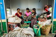 15 JUNE 2013 - YANGON, MYANMAR:  Passengers on the Yangon Circular Train. The Yangon Circular Railway is the local commuter rail network that serves the Yangon metropolitan area. Operated by Myanmar Railways, the 45.9-kilometre (28.5mi) 39-station loop system connects satellite towns and suburban areas to the city. The railway has about 200 coaches, runs 20 times and sells 100,000 to 150,000 tickets daily. The loop, which takes about three hours to complete, is a popular for tourists to see a cross section of life in Yangon. The trains from 3:45 am to 10:15 pm daily. The cost of a ticket for a distance of 15 miles is ten kyats (~nine US cents), and that for over 15 miles is twenty kyats (~18 US cents). Foreigners pay 1 USD (Kyat not accepted), regardless of the length of the journey.     PHOTO BY JACK KURTZ